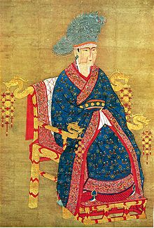 A painting of a woman in a blue dress with intricate gold and red decorations and a large blue hat. Her face has a simple angular design painted onto it in darker brown tones. She is sitting in a golden throne with dragon heads protruding from the ends of the armrests and from the sides of the top, back edge of the throne.