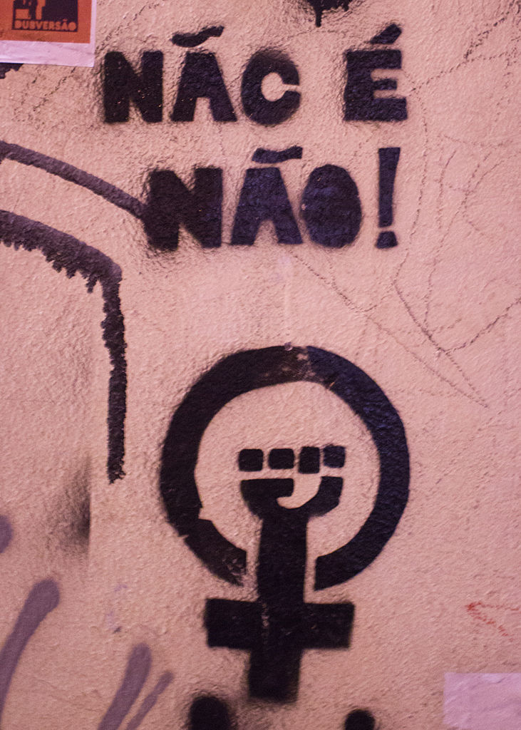 stencil graffiti of woman's symbol with a fist in the circle, beneath the words