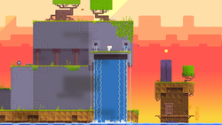 Gomez stands atop an anthropomorphic, purple structure with water falling from its orifices, as if it were crying. Trees grow atop the structure, grass lines the platforms, and the background is a deep yellow to orange gradient of a sunset. A bomb sits alone on the left side of the screen.