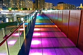Bridge at night with multicoloured LED lights lighting the bridge from below; each successive panel is lit in a different colour.