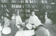 Gandhi seated on a library floor with several other people