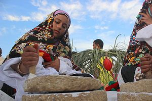 Siwa Oasis - Girl wearing the traditional dress of Siwa grinding salt