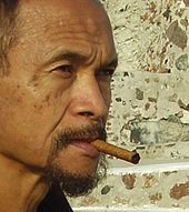 An older man, Goenawan Mohamad, smoking