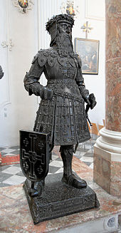 A statue of a knight with a long beard. He is wearing a crown of thorns and elaborate armour, he has a sword in his left hand, and a shield rests against his right leg.