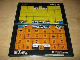 軍人将棋盤の一例。手前(オレンジ)は駒の種類がわかるように表向けに配置しているが、対局するときには奥(黄色)のように裏向けに配置する