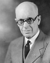 A photographic portrait of a bald white man with thick-rimmed glasses