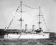 Black-and-white photograph of white ship with tall masts travelling on water.