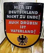 """Schwarz-rot-goldenes westdeutsches Schild mit der Aufschrift """"Hier ist Deutschland nicht zu Ende. Auch drüben ist Vaterland!"""""""
