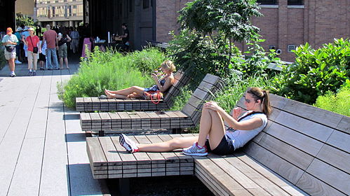 People sitting down on wooden chairs and reading books