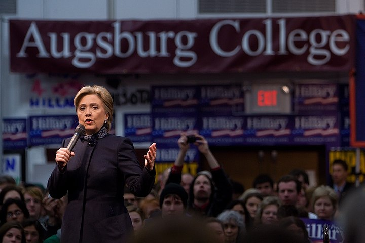 """Clinton speaking at a college rally as part of her 2008 Presidential campaign, with a crowd behind her looking on. She is speaking at Augsburg College in Minneapolis, two days before """"Super Tuesday"""", the day in 2008 when the largest number of simultaneous state-level elections was held. She is wearing a black suit. There are blue banners with the word """"Hillary"""" on them, hung around the room, as well as a large white-on-burgundy banner with the words """"Augsburg College""""."""