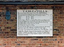 Antique table of bridge tolls now displayed on the outside of the toll house. Tolls range from a halfpenny for a pedestrian to two shillings for a large coach
