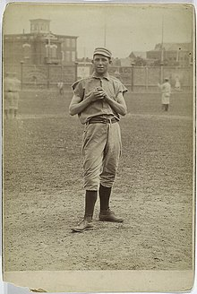A sepia-toned image of a young man in an old-style white baseball uniform and cap standing on a grass field holding a baseball in front of his chest with both hands
