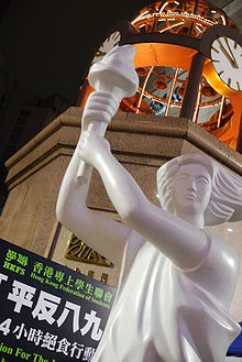 close-up view from below of a large white holding a torch; in upper background is large dome with clocks, a sign by the Hong Kong Federation of Students forms the lower part of the background