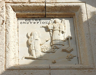 Onuphrius - Stone carving above the entrance of the Onuphrius monastery in Akeldama, Jerusalem (Potter's field). The image shows Onuphrius bowing down to an angel. Notable features are his long beard and leaf loincloth.
