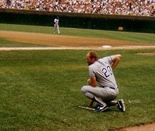 A man in a baseball uniform kneels looking in at the field.