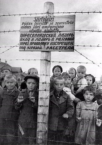 "East Karelian concentration camps - Staged photograph of Russian children at a formerly Finnish-run transfer camp in Petrozavodsk; photo taken by photographer Galina Sanko on 29 June 1944, one day after the Finns had left the area. The sign reads, in Finnish and Russian: ""Transfer camp. Entry to the camp and socializing through the fence are forbidden, violators will be shot."""