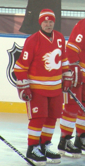 "A man stands in a full hockey uniform.  It is red with white and yellow trim and a large, white, stylized ""C"" logo.  He is wearing a red toque and has a large moustache."