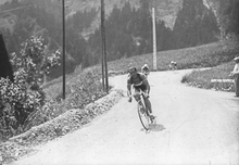 Photographie en noir et blanc d'un coureur cycliste dans la descente d'un col.
