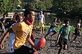 Lloyd, a senior player for the China Town AFL team runs with the football at the Lord Howe settlement football training, Honiara. AFL Development Officer, Michael Cormack in the Background (white top, yellow shorts). (10708476773).jpg