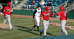 Batboy - A Lansing Lugnuts batboy (in white) carrying a baseball bat away from home plate.