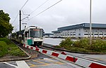 MAX light rail train passing PDX Cargo Center at airport (2015).jpg