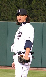 "A man wearing a white baseball uniform with a navy blue ""D"" on the chest, a navy blue cap bearing a white ""D"", and a baseball glove stands on a baseball field"