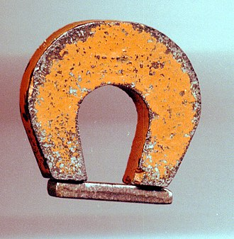 "Magnet - A ""horseshoe magnet"" made of alnico, an iron alloy.  The magnet, made in the shape of a horseshoe, has the two magnetic poles close together.  This shape creates a strong magnetic field between the poles, allowing the magnet to pick up a heavy piece of iron."