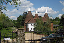 A photograph of two oast houses. There are four cone-shaped kilns topped by white cowls rising from the v-shaped roofs of the houses