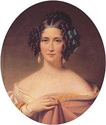 Un portrait d'une jeune femme aux cheveux bruns richement coiffés, attachée avec un arc bleu