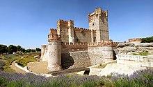 Un castello di pietra, circondato da un fossato vuoto.