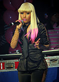 A portrait of Nicki Minaj in a black outfit singing into a microphone.
