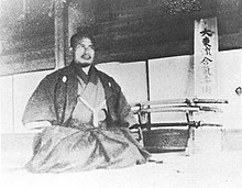 A kneeling man in kimono in front of a sword stand