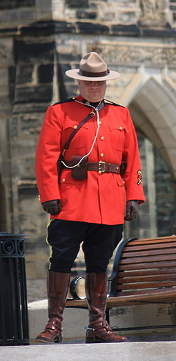 A Royal Canadian Mounted Police officer in the force's distinctive dress uniform Mountie-on-Parliament-Hill.jpg