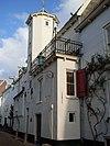 foto van Huis met gepleisterde gevel met traptorentje, gesmede muurankers en uitbouw aan de straat. Rechte kroonlijsten