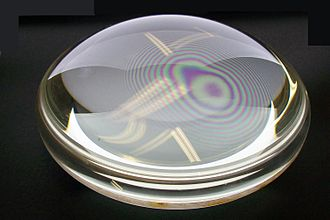 Newton's rings - Newton's rings seen in two plano-convex lenses with their flat surfaces in contact.  One surface is slightly convex, creating the rings.  In white light, the rings are rainbow-colored, because the different wavelengths of each color interfere at different locations.