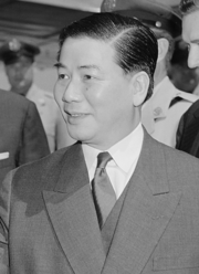 A portrait of a middle-aged man, looking to the left in a half-portrait/profile. He has chubby cheeks, parts his hair to the side and wears a suit and tie.