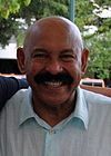 A man with a thick mustache is wearing light blue shirt.