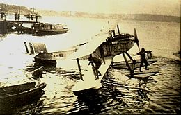 Single-engined biplane with floats, parked on water, with one crewman on float and another on lower wing
