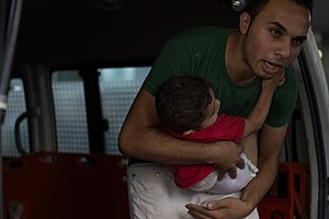 Timeline of the 2014 Israel–Gaza conflict - Palestinian man with child, 8 July