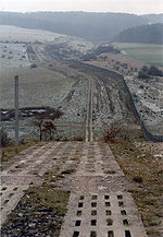 A patrol road, made of two parallel rows of perforated concrete blocks, performs a steep descent into a valley. To the right, running parallel to the road, is a continuous fence. The road and fence continue into the distance, crossing fields that are dusted with a light sprinkling of snow, and ascending another hillside on the far side of valley. Dark forests loom in the distance.