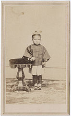 Photograph of a young Chinese boy standing next to a table.jpg