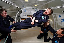 Hawking, without his wheelchair, floating weightless in the air inside a plane