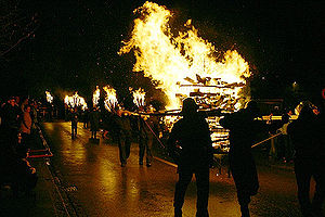 Chienbäse - Carriers moving a bonfire in a carrying cage. Chienbäse bearers are visible in the background.