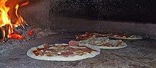 Pizze appena infornate in un forno a legna
