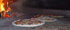 A wood-burning pizza oven baking pizzas at Mau...