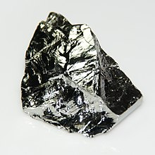 Grayish lustrous block with uneven cleaved surface.