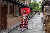 Portrait photograph of a walking woman wearing a red yukata with an oil-paper umbrella, in Gion, Kyoto, Japan.jpg