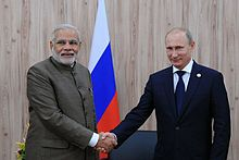 Two standing men are pictured shaking hands. The first is dressed in Indian clothing; the second is in a Western business suit; both standing behind a Russian flag.