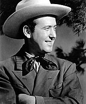 A man wearing a light-coloured cowboy hat, neckerchief and dark jacket