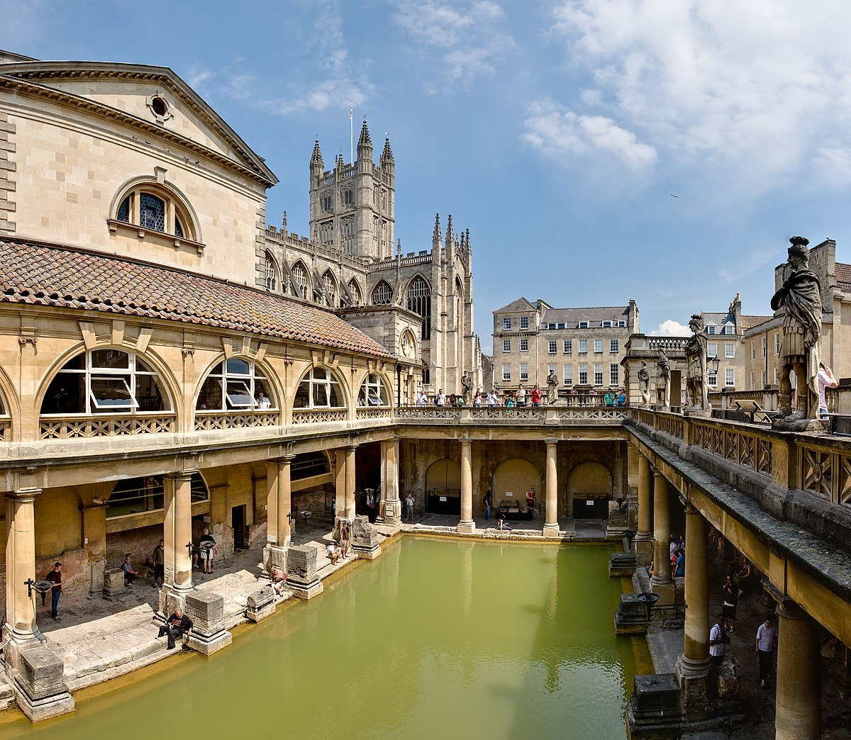緑色の水をたたえた矩形の領域を黄色の石造りの建物の柱が囲んでいる浴場の写真。背後に見えるのは修道院の塔。